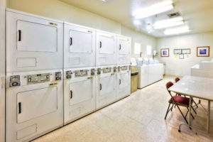 Laundry Room with at least 8 washers and 8 dryers, table and chairs