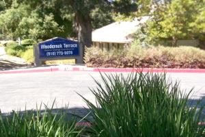 "Woodcreek Terrace sign ""Senior Living Community"", (916 )773-9078, entrance road"