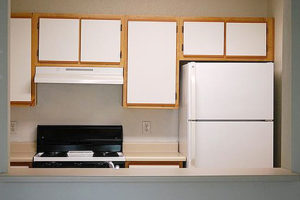 Kitchen, white refrigerator, black stove, white cabnet doors with brown outer paneling